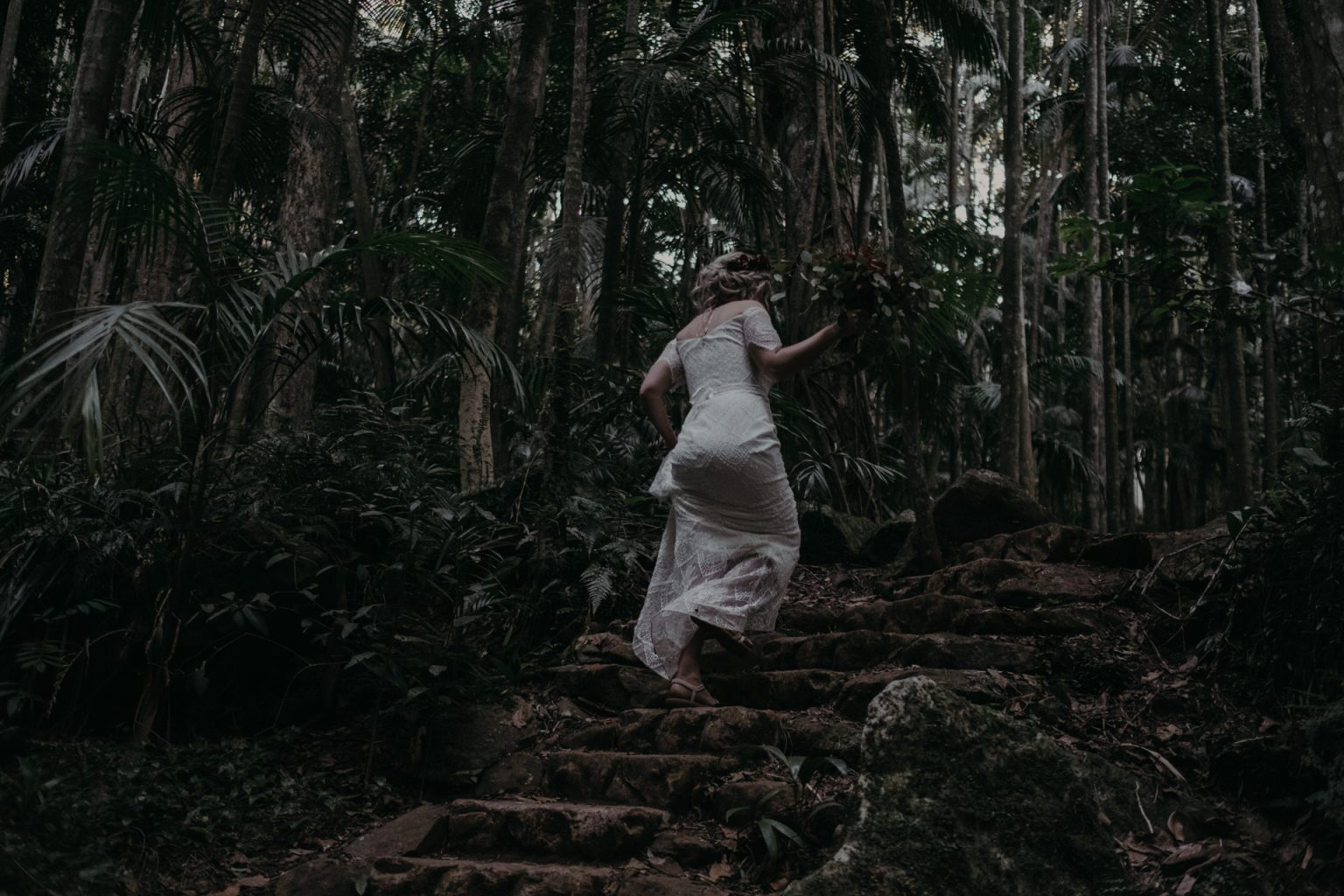 bride in forest walking up stairs
