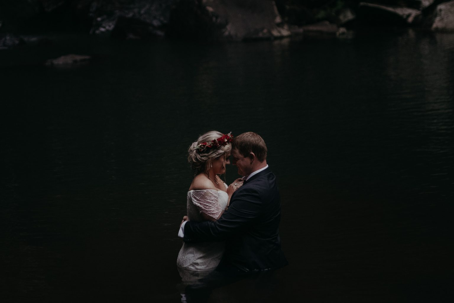 bride and groom in rock pool forest