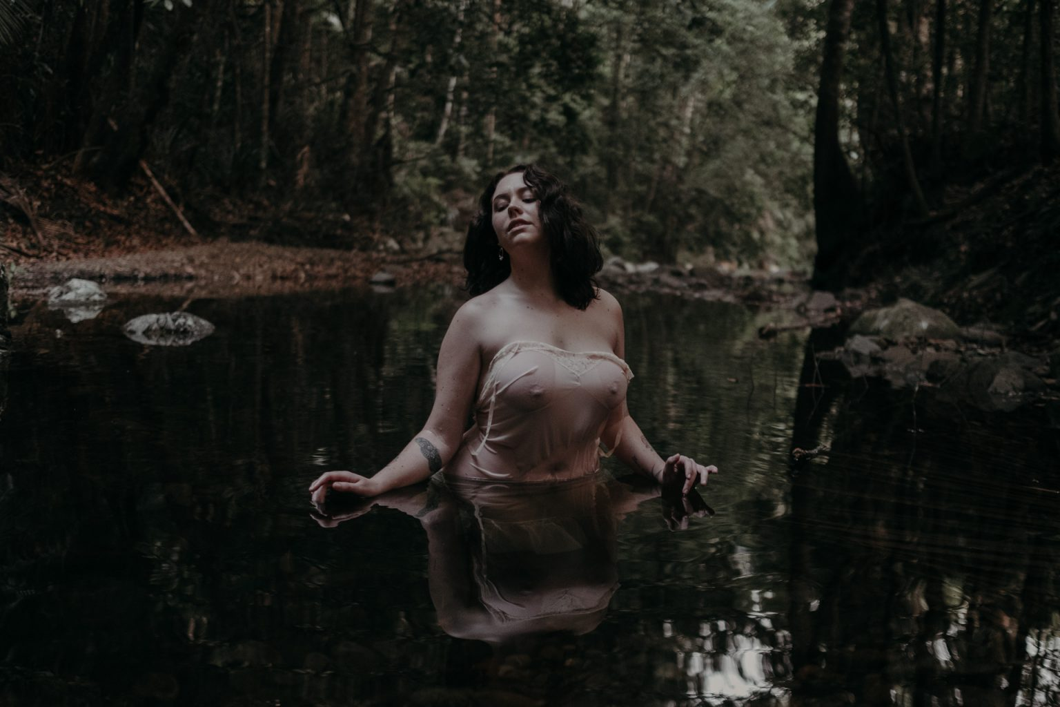 woman in see-through dress in forest pool