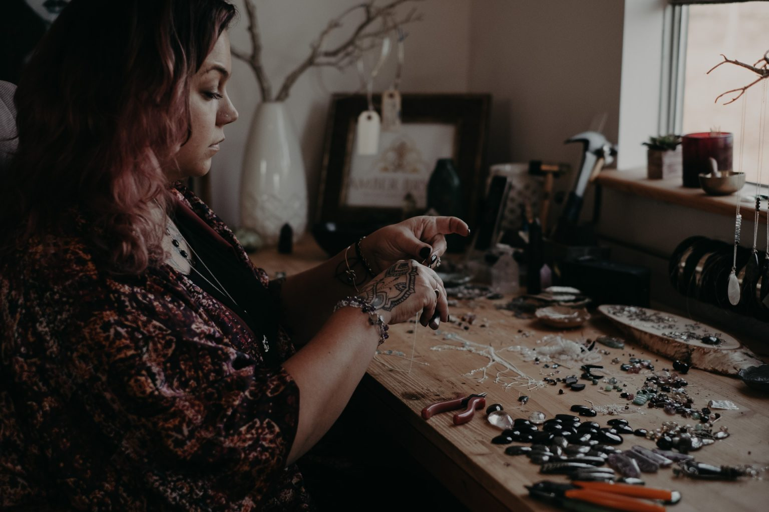 woman making jewellery at table