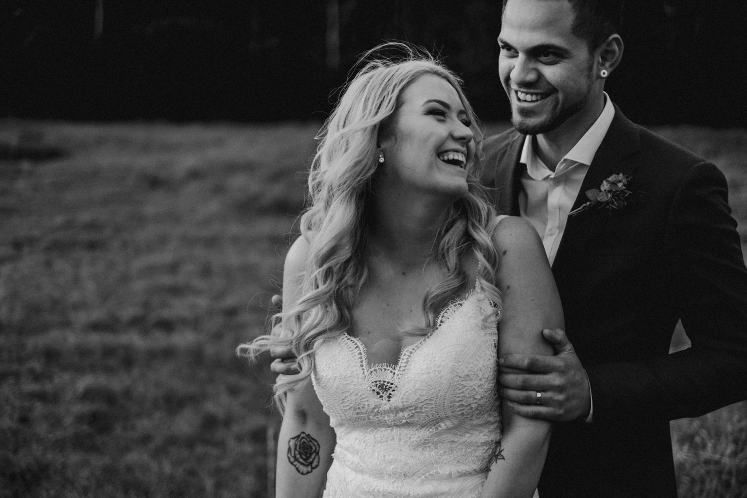bride and groom in field long grass laughing
