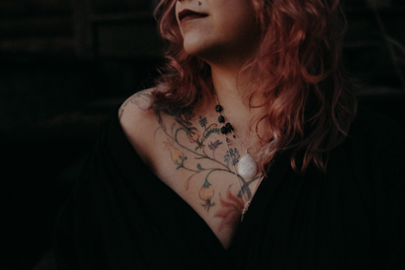 portrait of woman in woods with tattoos pink hair