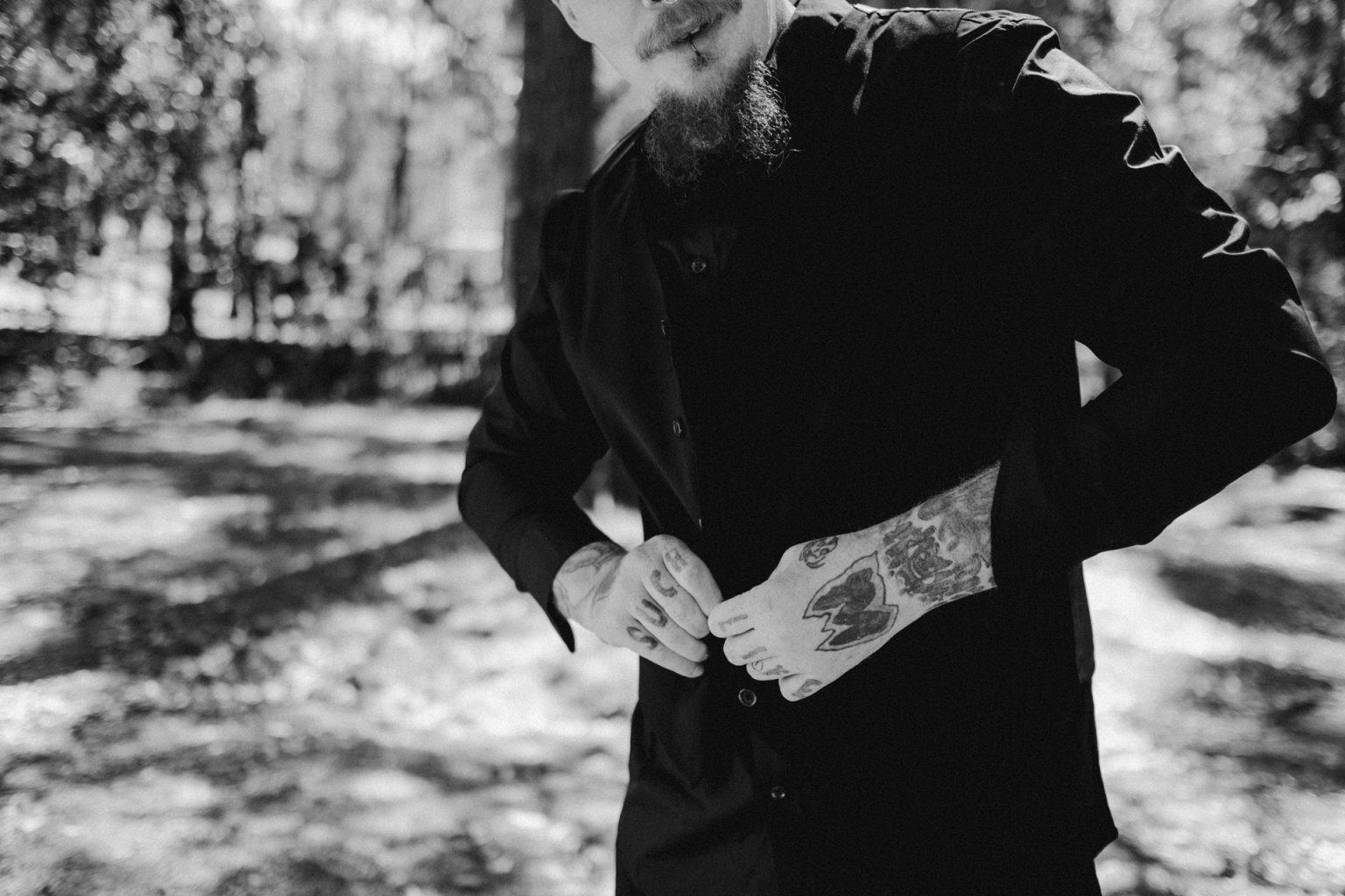 tattooed man doing up shirt