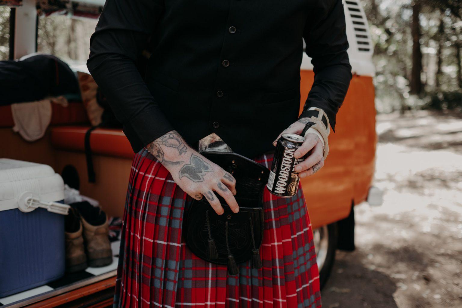 tattooed man putting on kilt