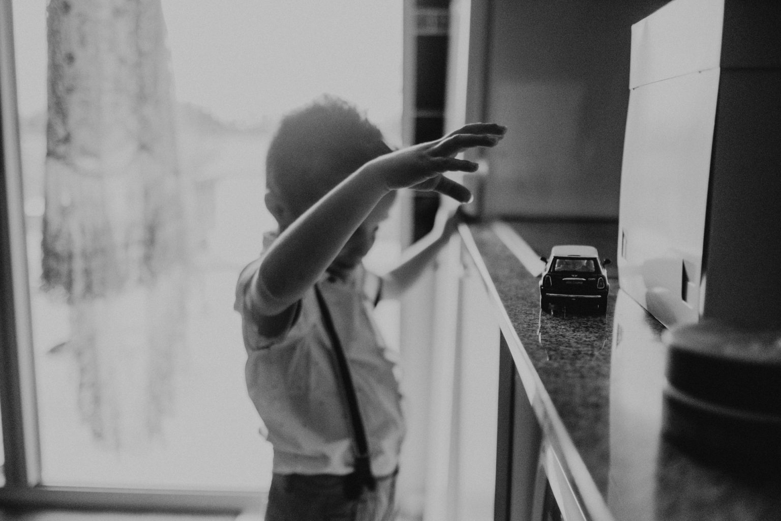 boy playing with small car