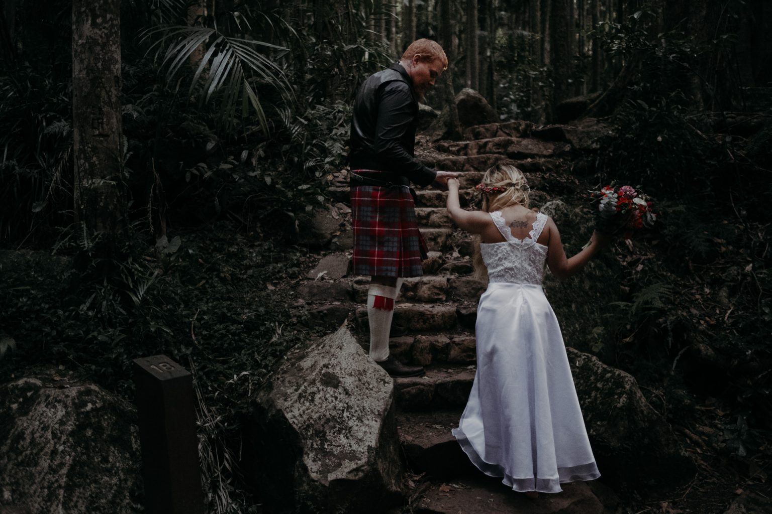 groom helping bride up stairs forest