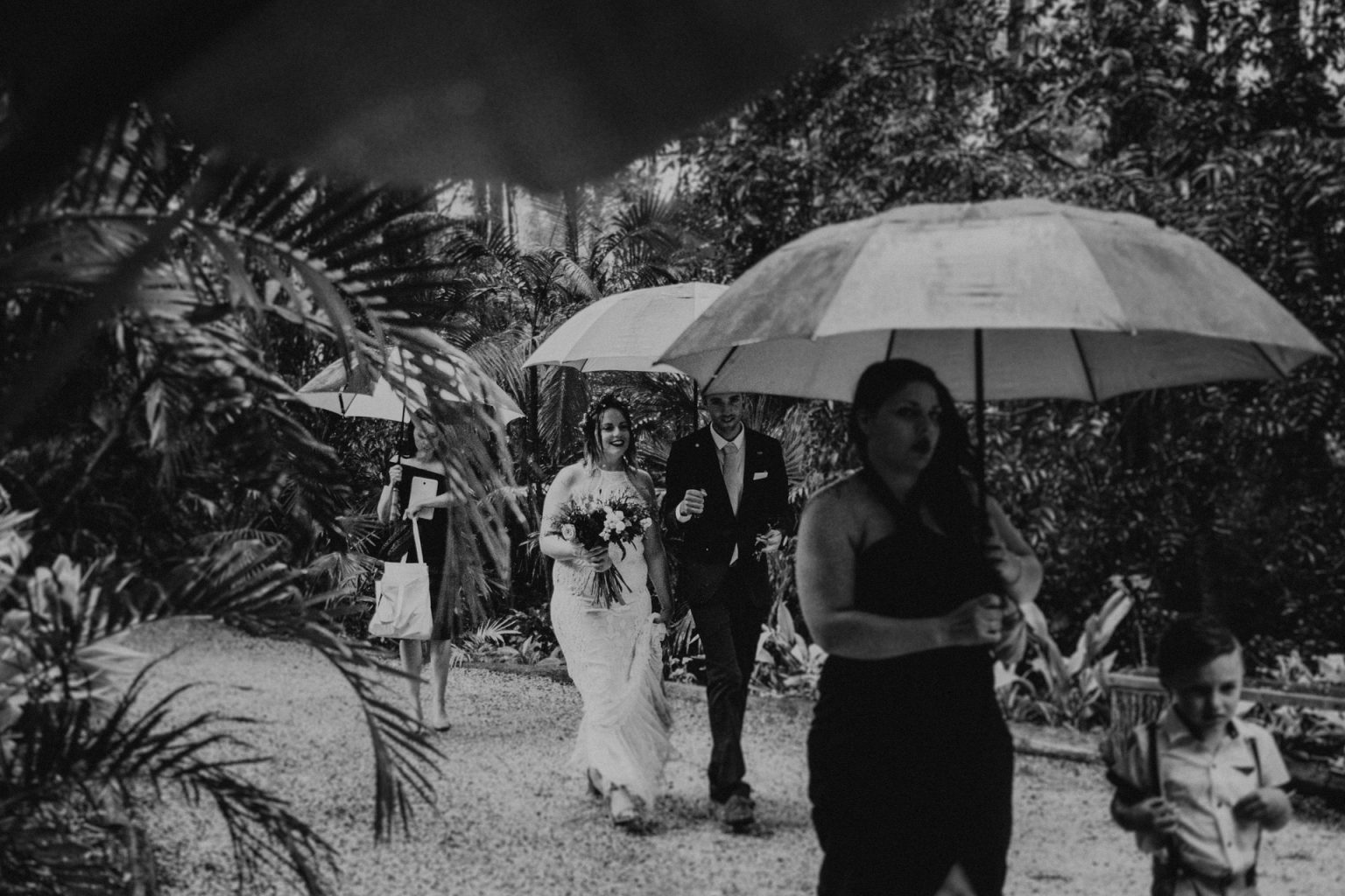 bridal party with umbrellas in forest