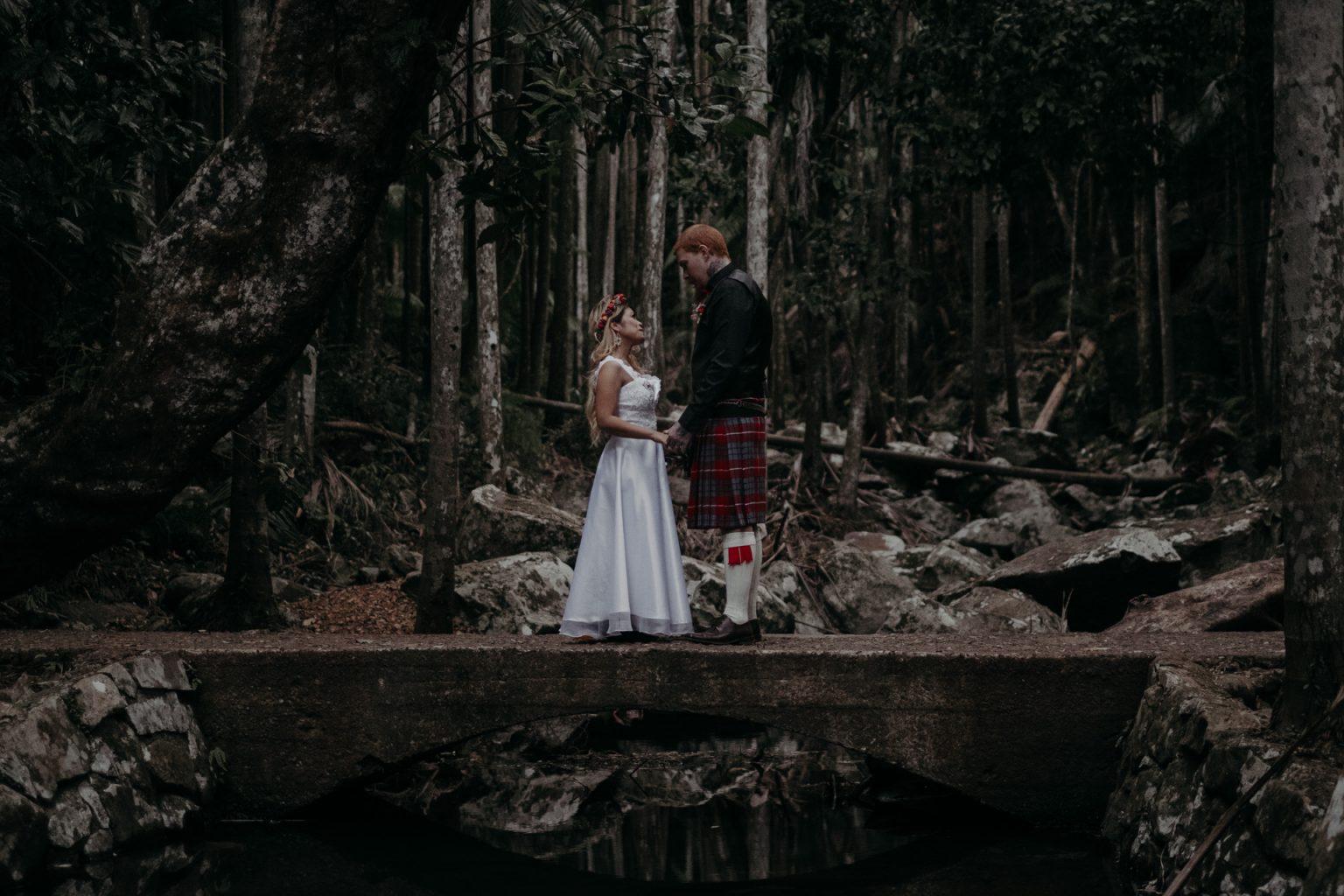 bride and groom on bridge in forest elopement mt tamborine