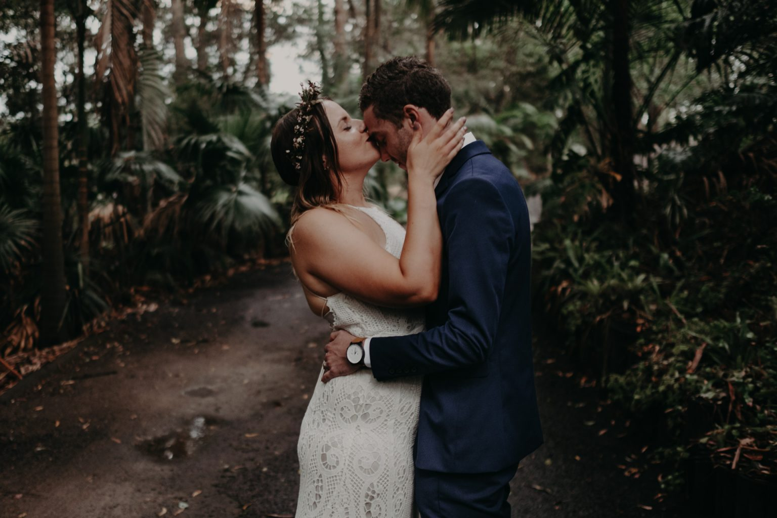 bride kissing groom head forest