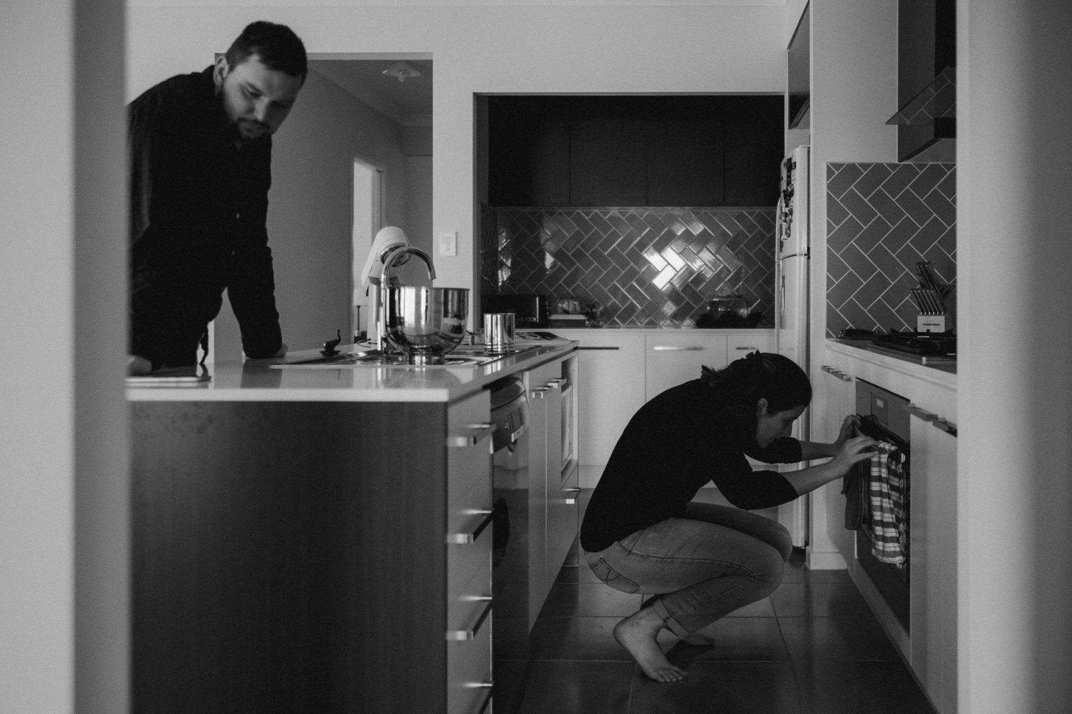 man and woman in kitchen making cupcakes