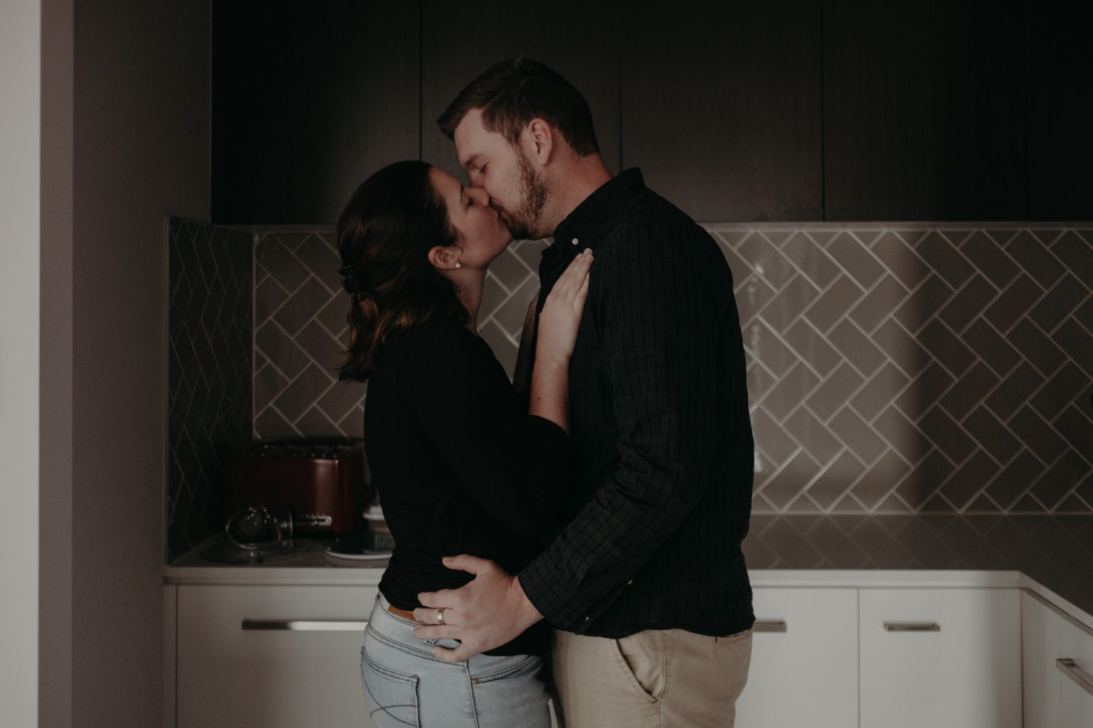 man and woman kissing in kitchen