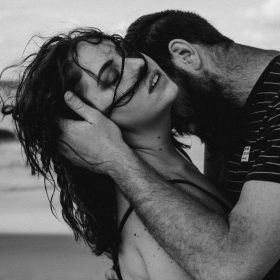 man kissing woman neck on beach sexy curls brunette