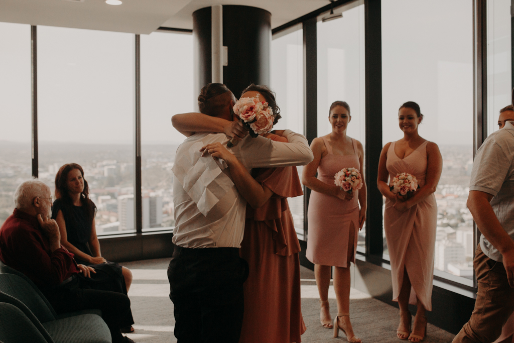 Groomsman hugging bridesmaid at Brisbane Registry RBDM