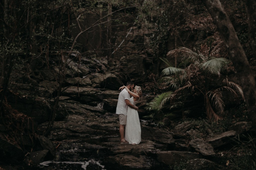 bride and groom walking on rocks  at Kumbartcho Sanctuary at Eatons Hill