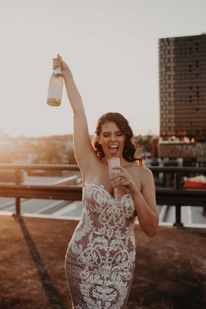 bride drinking on  rooftop for New York style elopement in Fortitude Valley Brisbane sunset