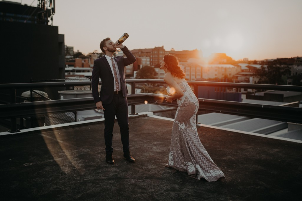 groom drinking champagne  on  rooftop for New York style elopement in Fortitude Valley Brisbane sunset