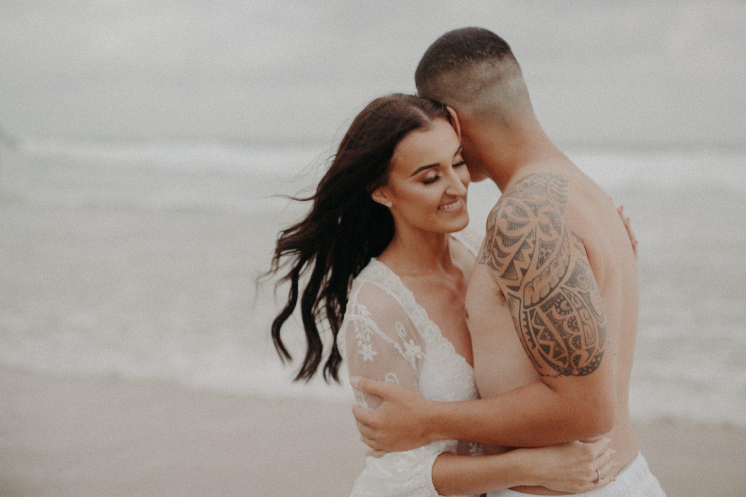 tattooed man and woman wearing lace on beach