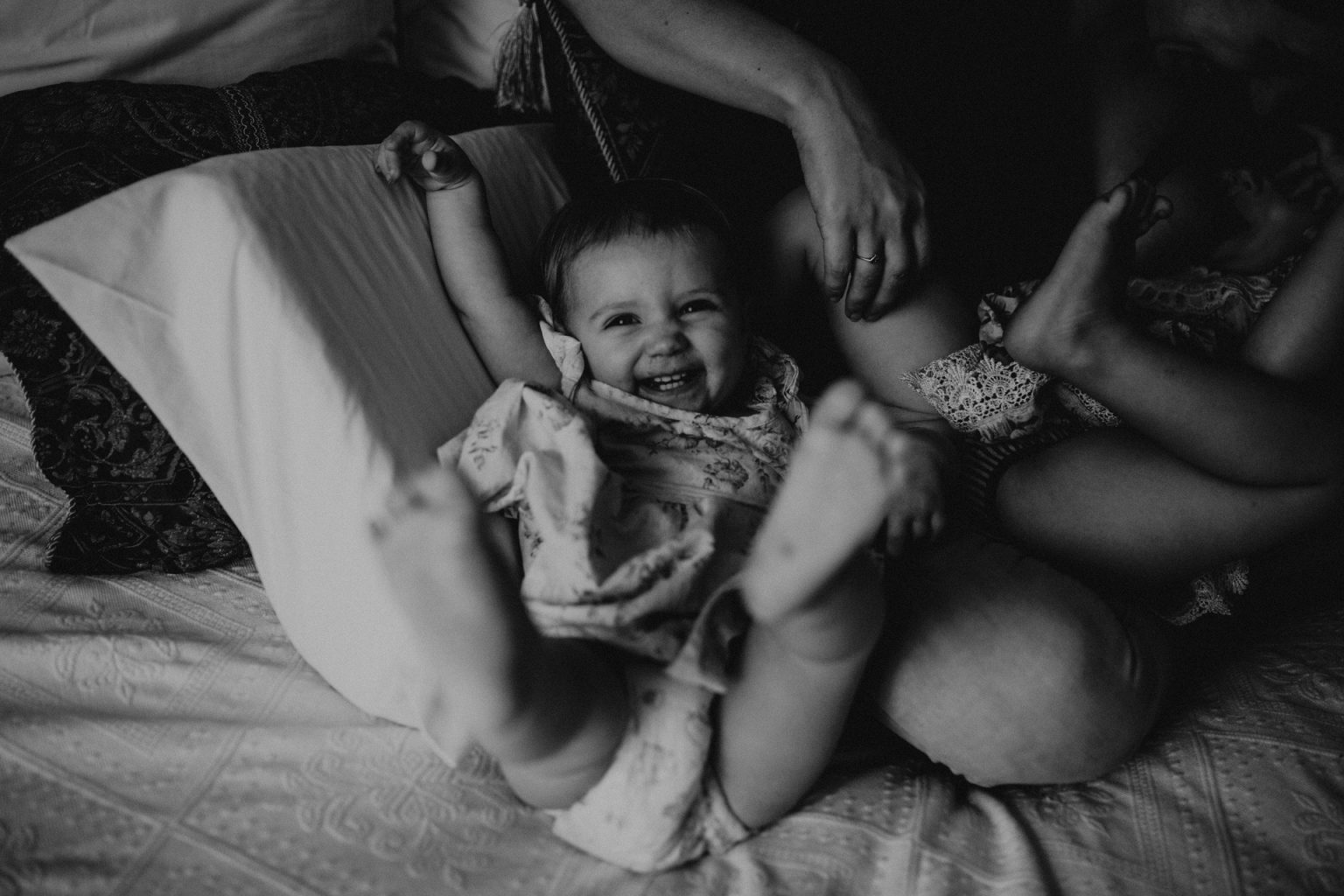 Girl being tickled on bed
