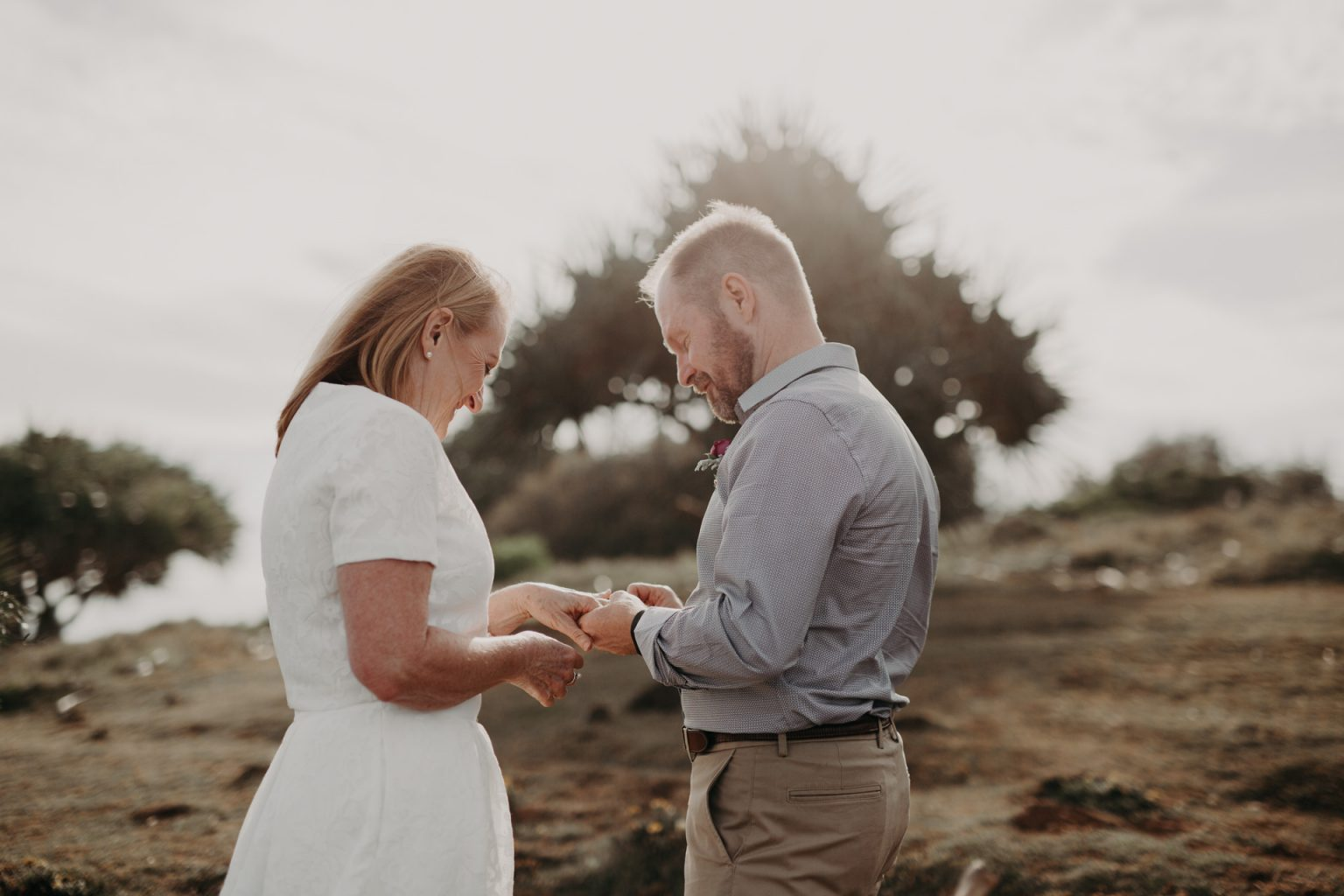 bride and groom exchange rings at clifftop elopement