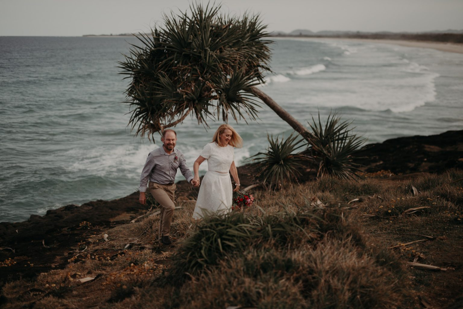 bride and groom explore rocks Fingal head