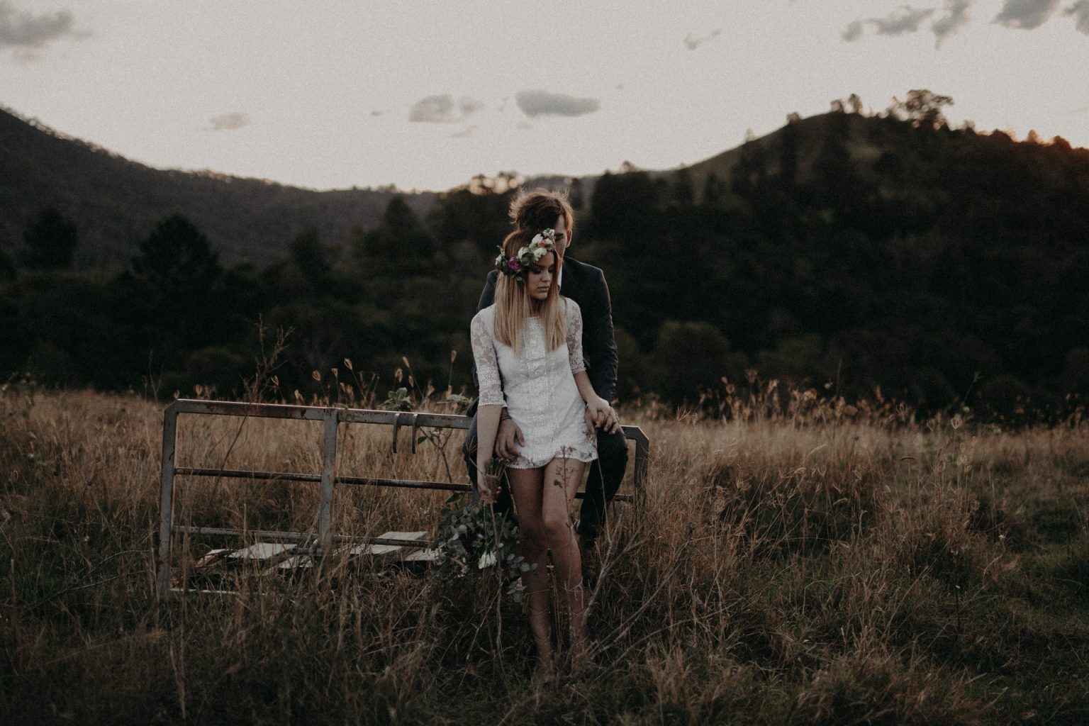 bride and groom on fence road long grass scenic rim
