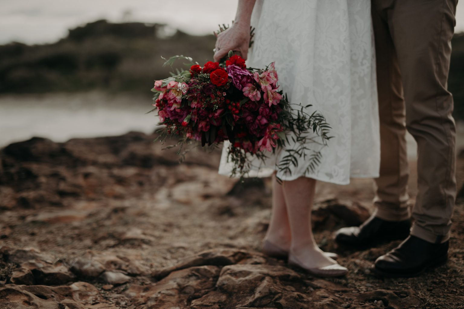 bride on clifftop with flower bouquet