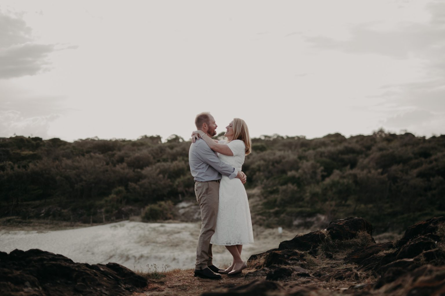 bride and groom standing on clifftop Fingal head