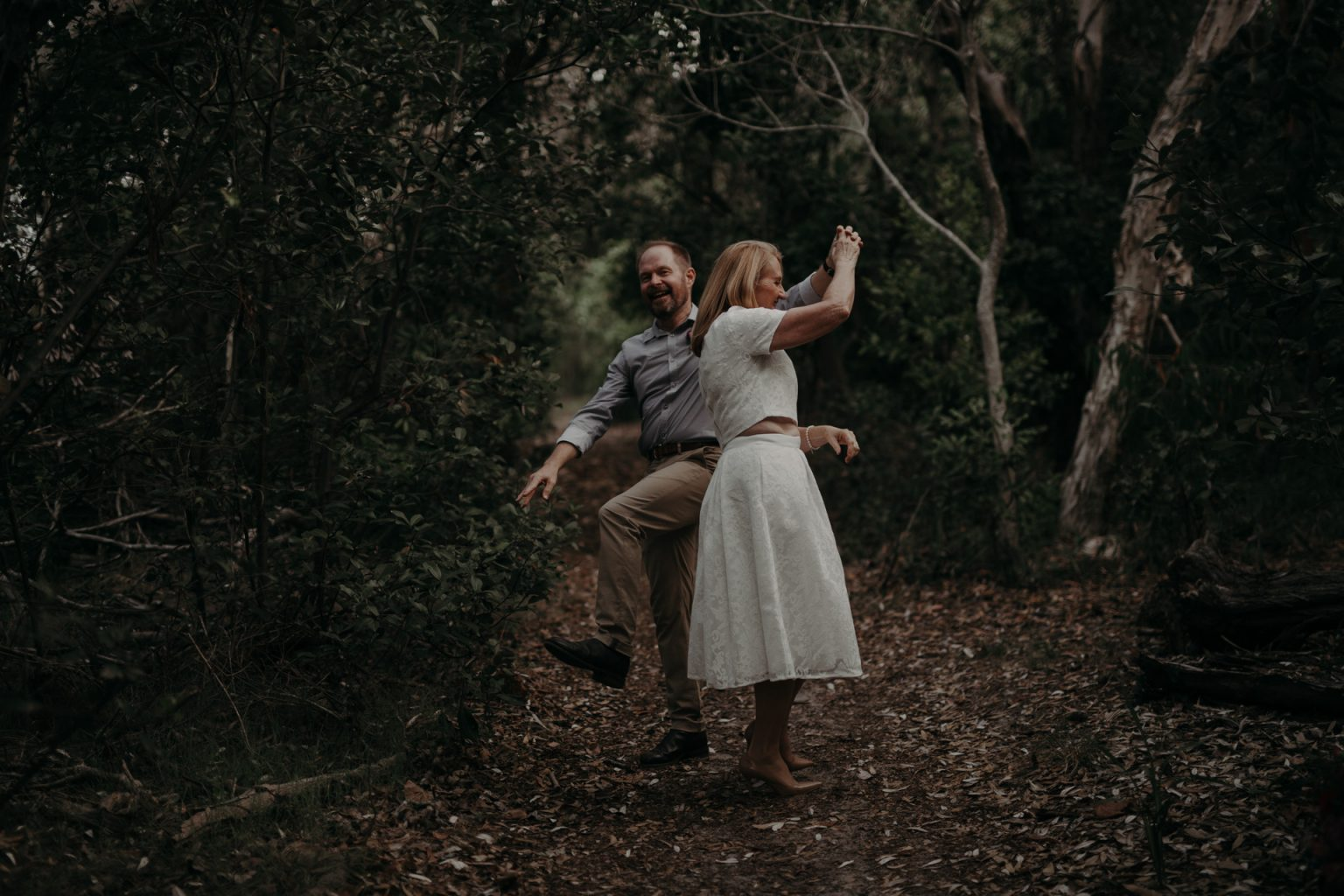 bride and groom dance in forest at Fingal head