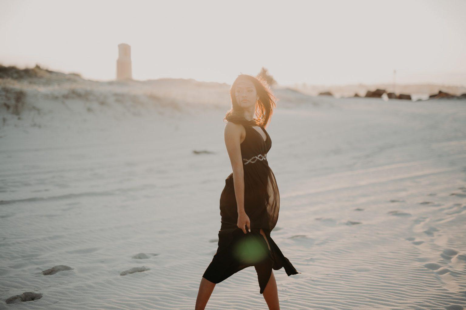 woman on beach windy hair brunette sun glare